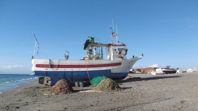Grote en kleine boten staan geparkeerd op houten balken op het strand.